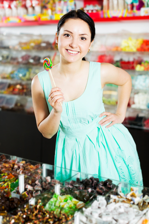 Happy adult girl posing to photographer with lollypop at candies shop