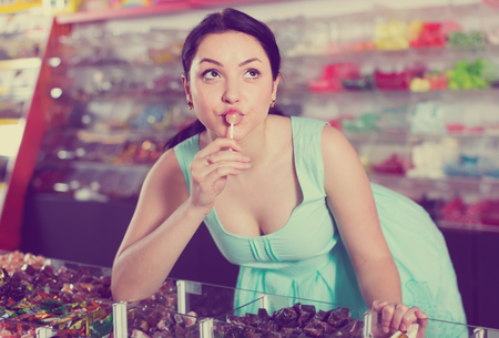 Young girl posing in the store with lolly on the background of counters with sweets