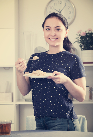Young woman having healthy breakfast with cereal and smiling
