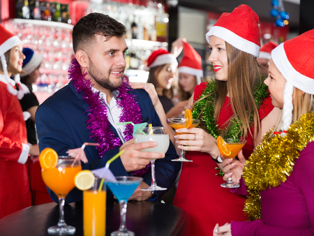 Cheerful guy with two girls funning and toasting drinks on new year eve party at bar