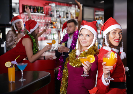 Happy young female colleagues enjoying corporate new year party in bar