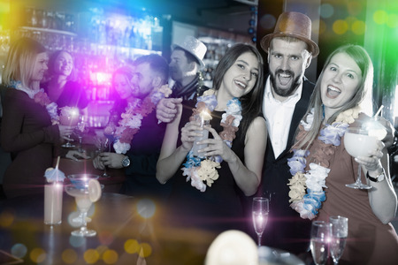 Happy young man with female friends enjoying party in Hawaiian style in bar Stock Photo