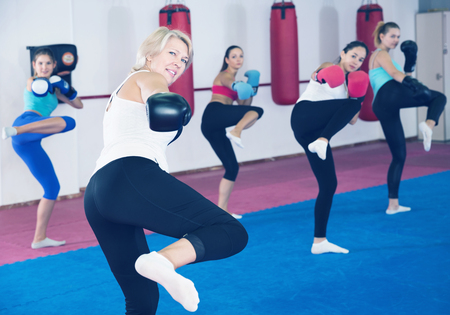 Portrait of sporty elderly woman who is boxing in group in gym.
