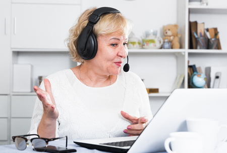Mature woman communicates via the Internet with friends or relatives Foto de archivo