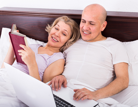 Mature couple burring with laptop in bedroom in apartment
