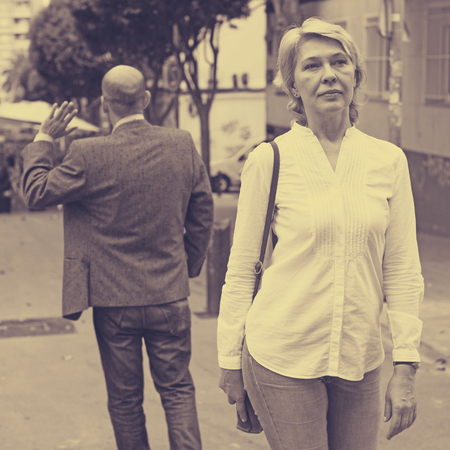 Portrait of annoyed mature woman standing away from man standing back to her  Banco de Imagens