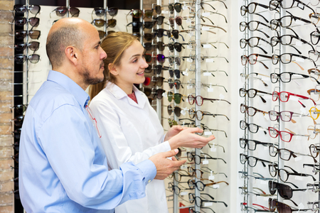 Happy female ophthalmologist and mature patient in modern optics store. Focus on the man