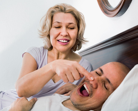 Mature exhausted  girl looking at snoring boyfriend sleeping tight