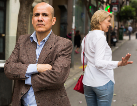 Portrait of annoyed mature man standing away from arguing woman outdoors