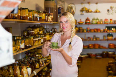 cheerful female customer picking ceramic cup in ceramics workshop Stock Photo
