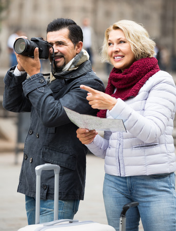 positive european mature couple with suitcases, camera and map outdoors