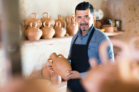 Cheerful man sculptor having ceramics in hands and standing in pottery atelier Stock Photo
