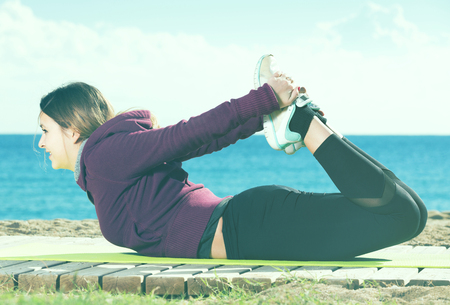 Laughing girl exercising on exercise mat outdoor