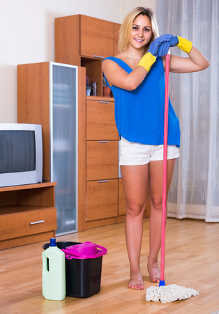 Young happy housewife smiling and doing floor cleaning indoors