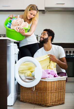 Happy young mixed spouses doing regular laundry and smiling