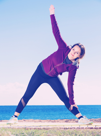 Smiling cheerful woman doing youga at beach Stock Photo