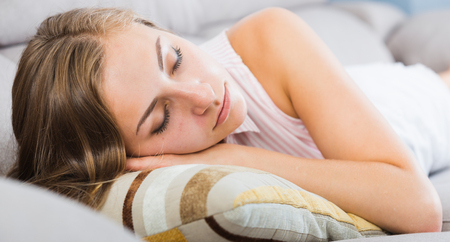 Young woman lying and peacefully sleeping on sofa at home Stock Photo