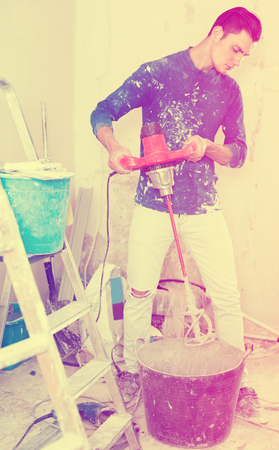 concentrated builder mixing plaster in bucket using electric mixer in repairable room Stock Photo