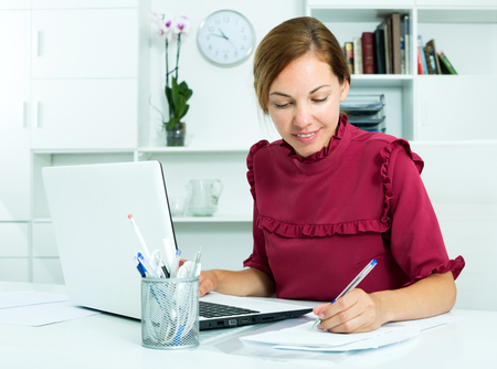 Beautiful business woman working at office with laptop and taking notes