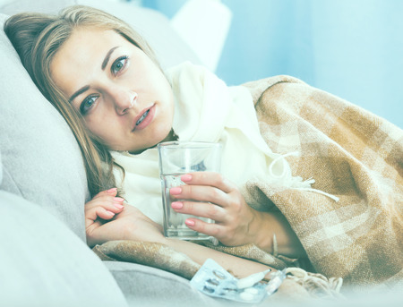 Ill girl wrapping in blanket on couch with drink and medicine in arms