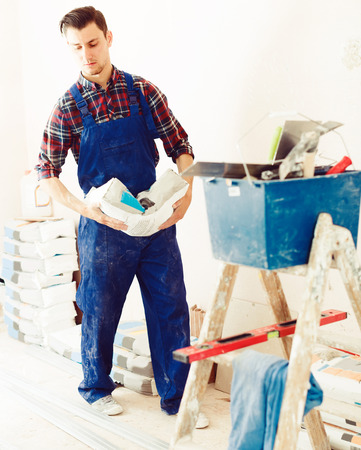 Young handyman going kneading putty during house renovation
