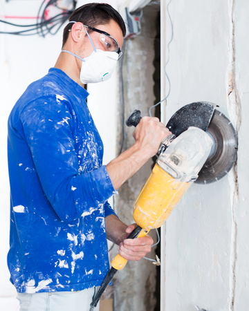 concentrated construction worker cutting concrete wall by using handheld circular saw in repairable room Stock Photo