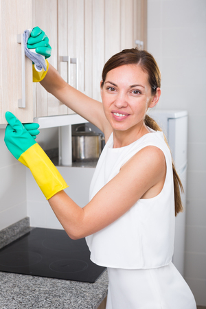 glad young woman cleaning at home wearing protective apron and gloves Standard-Bild