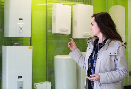 Young longhaired woman choosing heating water converter in hypermarket  Reklamní fotografie