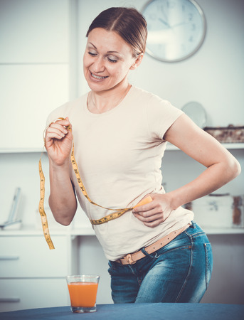 Smiling young woman measuring waist with yellow tape Imagens