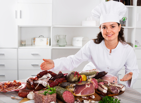 Young happy girl cook costs near table on which sausages and smoked meat lie Stock Photo