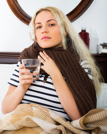Portrait of blonde young girl with fever wrapping herself in scarf indoors