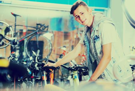 Smiling boy teenager choosing special  bicycle in sport hypermarket