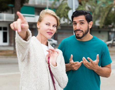 Man is asking woman stranger about road to hotel in the city. Stock Photo