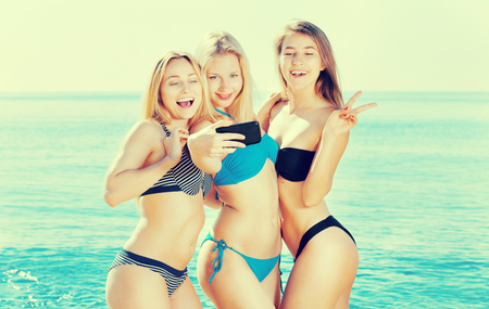 Three young women friends looking happy taking mobile self photo in bikini on a sandy beach. Focus on all persons