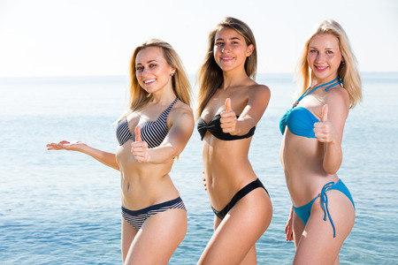 three smiling attractive girls looking happy in bikini on beach   Stock Photo
