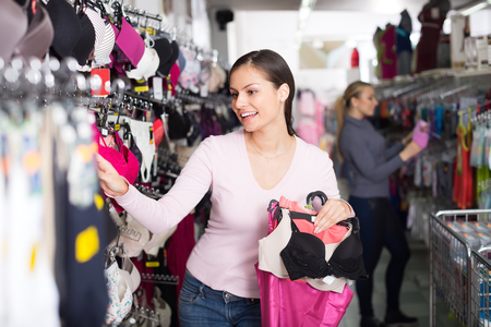 Happy smiling young woman selecting new bra in lingerie department