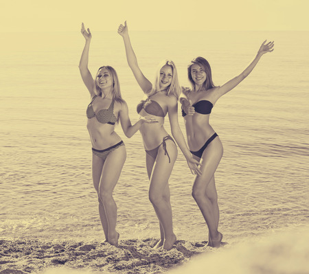Three young playful girls wearing swimwear standing on beach together and smiling