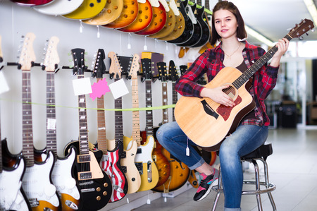 Female rock-n-roll player is deciding on acoustic guitar in guitar shop.  Stock Photo