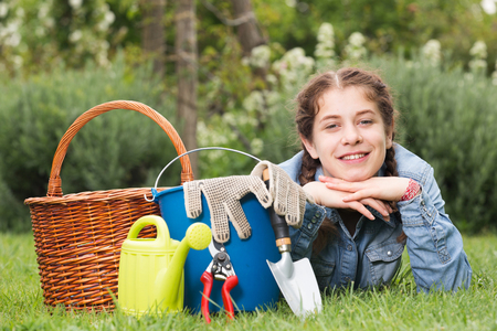 happy female with gardening tools while lying in park