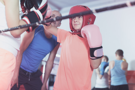 Group of kids exercising with instructor on boxing ring at gym Stock Photo