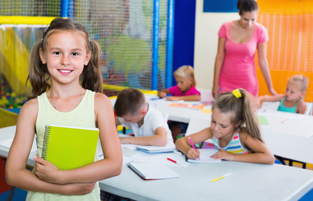 Portrait of smiling diligent pupil girl studying in school class