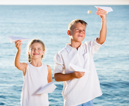 smiling boy and girl playing with origami plane toys on beach on summer day Foto de archivo