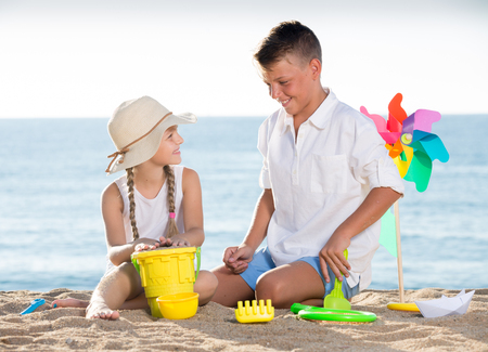 portrait of smiling boy and girl sitting and playing with bright plastic toys on beach  Foto de archivo