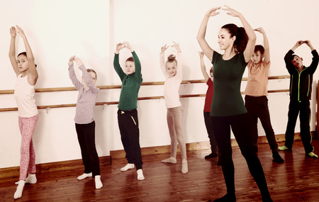 Group of happy american children practicing at the ballet barre