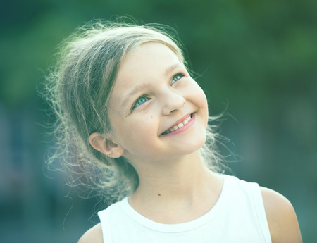 closeup portrait of happy girl in elementary school age outdoors  Stock Photo