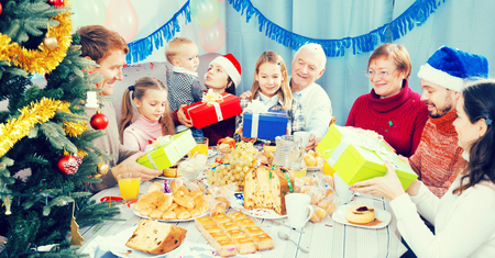 Large family handing the gifts to each other during Christmas dinner