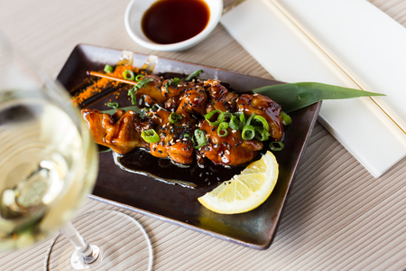 japanise style grilled chicken yakitori beautifully served on the plate with side souse