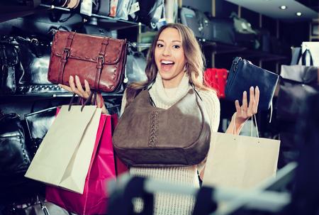 Young joyous woman buying leather purse in haberdashery shop Stockfoto