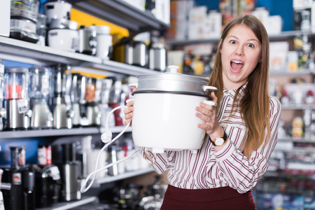 Attractive girl in delight from new devices in shop of house appliances  Stock Photo