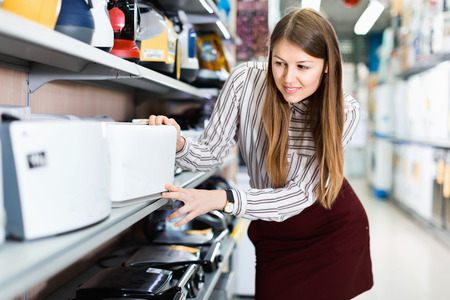 Modern glad positive female housewife choosing new toaster in domestic appliances section